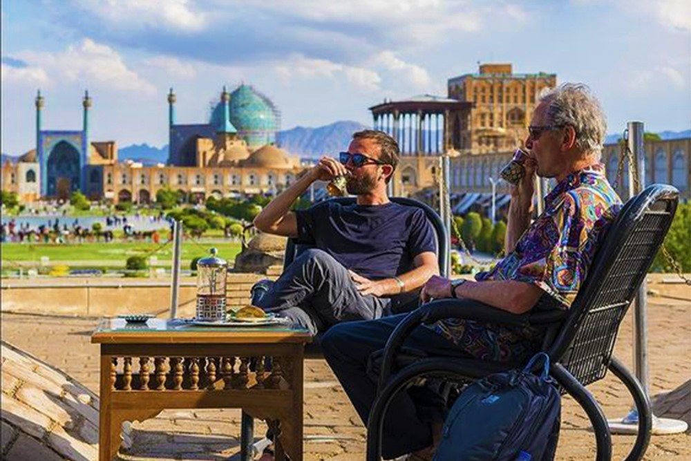 Travel to Iran: tourists enjoy their herbal drink in Isfahan