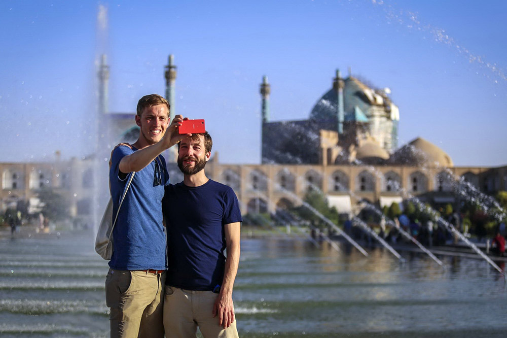 Travel to Iran, tourists take a selfie in front of Imam Mosque in Isfahan